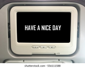 """Airplane monitor behind passenger seat with black screen and word """"Have A Nice Day""""."""