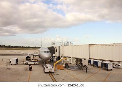 Airplane near the terminal in an airport. Trucks and ladder near airplane.