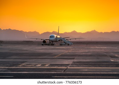 Airplane on the Runway at the Airport in the Evening Against the Backdrop of the Mountains