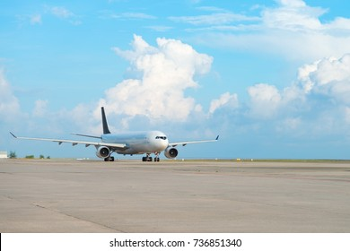 Airplane on runway strip in an airport with cloudy sky on background