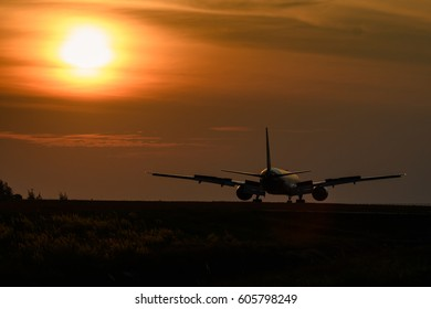 Airplane on tropical runway in sunset