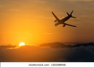 Airplane over the clouds, The plane on a background of during sunset.