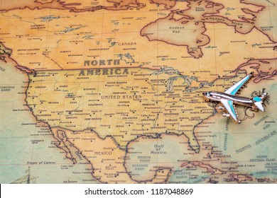 Airplane over a map of North America close-up. Toy airplane on the map background.