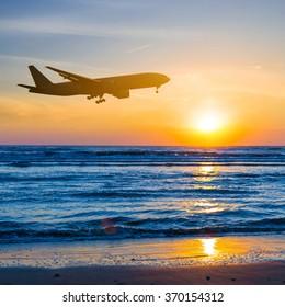 airplane over a sea coast sunset
