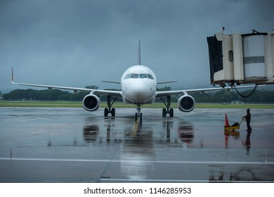 Airplane parking at the airport bay in the rainy day