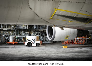 Airplane parking for maintenance service check by technician. Aircraft mechanic disassembly exhaust sleeve and air inlet from jet engine of aircraft.