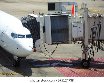 An airplane parks and has a Jetbridge that links the passengers to the terminal.