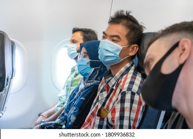 Airplane passengers are wearing medical masks on their faces. Air travel during the coronavirus pandemic. Airlines requirements. Kuala Lumpur / Malaysia - 04.27.2020
