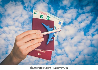 Airplane, passport and money in female hand on blue sky background - travelling concept - retro style