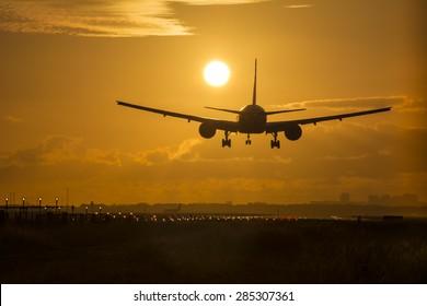 Airplane preparing for landing during sunrise.