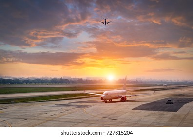airplane ready for boarding in a airport hub at sunset