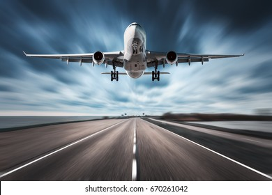 Airplane and road with motion blur effect. Landscape with white passenger airplane is flying in the cloudy sky over the asphalt road. Blurred. Passenger airplane is landing. Commercial plane. Aircraft