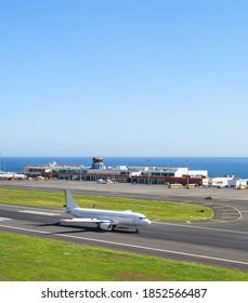 Flugzeug auf Start- und Landebahn, Flughafen-Terminal im Hintergrund, Saisonlandschaft, Madeira, Portugal