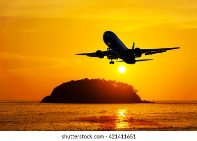 Airplane with seascape and sky sunset in twilight,  Plane with sea sunset, plane in colorful sky or transport plane, Plane come down on the land