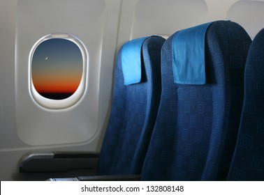 Airplane seat and window inside an aircraft with view of new moon at sunset.