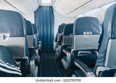 Airplane seats in the cabin economy class with sunlight