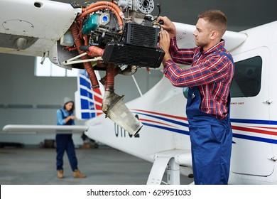 Airplane service team repairing plane in hangar:  modern mechanic fixing disassembled airplane turbine