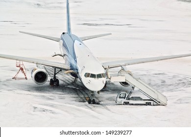 Airplane and servicing car at snowy airport