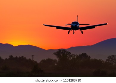 Airplane silhouette approaching runway for landing on airfield on sunset dusk with colorful orange and red sky over a mountain. Concept for summer time holiday adventures leisure sport and recreation.