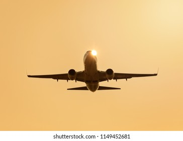 Airplane silhouette. Plane taking off. Sunburst. Colorful sundown