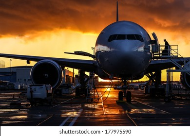Airplane silhouette, storm cloud low ceiling during sunset on background, look like fire