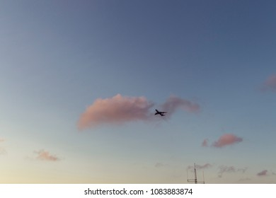 Airplane silhouette at sunset on lightly cloudy sky