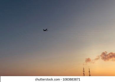 Airplane silhouette at sunset, orange sky