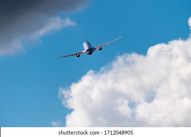 Airplane in the sky. Aircraft between clouds backside shot