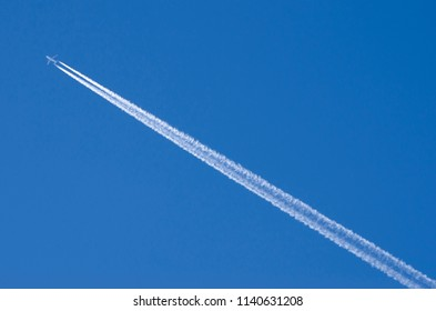 Airplane in the sky with contrails
