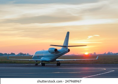 Airplane stay in airport. Business jet on the apron for aircraft. The background of the city