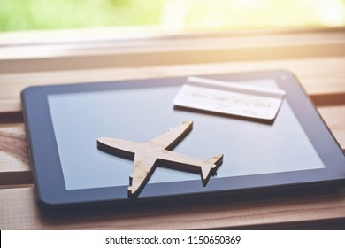 Airplane symbol with credit card and tablet computer. Online ticket booking concept