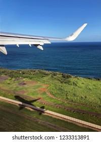 Airplane take off with plane shadow on runway on Kauai, Hawaii