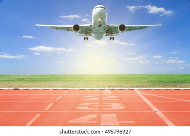 Airplane take off with Start and Finish point of race track ,Running track number in front of tracks in stadium with grass and blue sky scenery background,open high season travel and tour concept