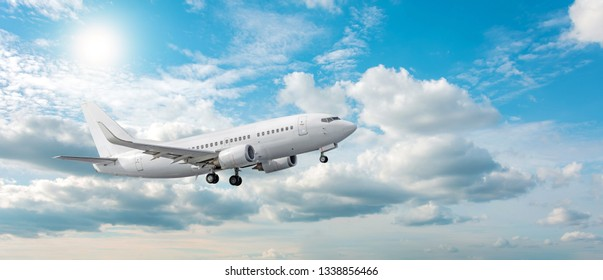 Airplane takes off against the background of the panorama of clouds and the sun