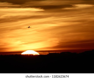airplane takes off against the sun and sky