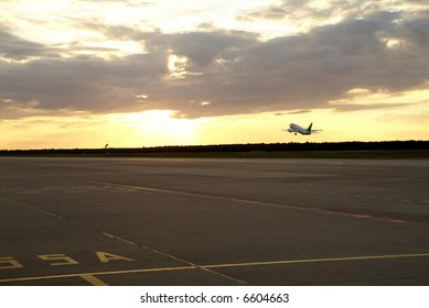 an airplane takes off the airport at sunrise