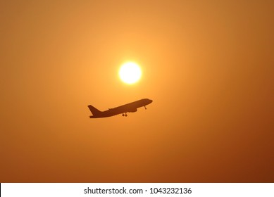 Airplane taking off against rising sun. Travel concept.