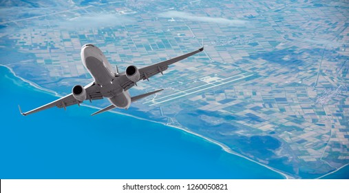 Airplane taking off from the airport -  Passenger airplane is flying in blue cloudy sky over the sea