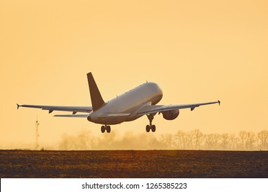 Airplane taking off from airport runway at sunset.