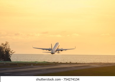 Airplane taking off during a beautiful sunset above the sea. Silhouette of plane fly up at wonderful sunset yellow sky background. Vacation, aviation, travel, summer concept, copy space