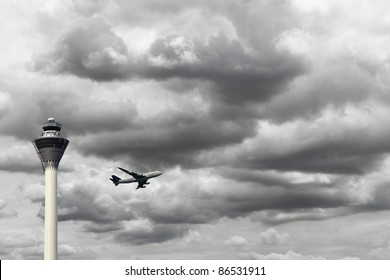 An airplane taking off during a stormy cloudy day overlooking the airport control tower.
