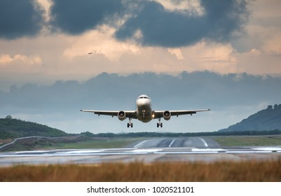Airplane taking off in summer day front view, horizontal, rain clouds on background/ Plane fly up/ Take off aircraft from the airport, low over the runway Vacation, aviation, travel, trip - concept