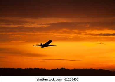 airplane taking off in sunset