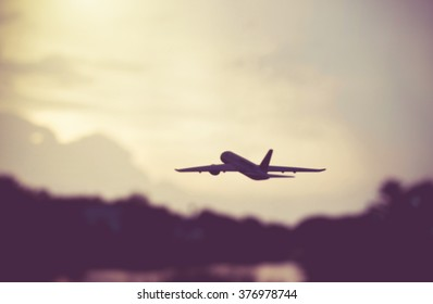 Airplane taking off at sunset. Silhouette photo.Photo is blur.