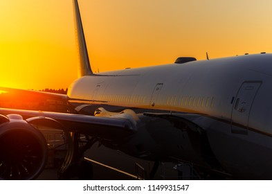 Airplane at terminal gate in international airport at sunrise.