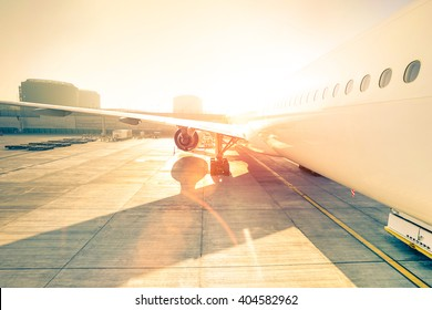 Airplane at terminal gate ready for takeoff - Modern international airport at sunset - Travel concept around the world - Wide angle distortion with rose quartz filter and enhanced sunshine lens flare