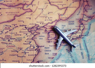 Airplane toy on North Korea and South Korea part of world map. International flights to North/ South Korea concept.