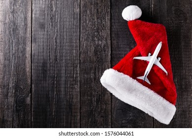 Airplane toy on Santa Claus hat on wooden rustic background. Christmas and new year celebration. Winter holidays. Top view