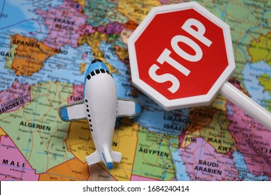Airplane Traffic Limitations. Air traffic stopped.Air travel prohibited.Ban on air travel.Coronavirus epidemic problem. Decorative airplane and stop sign on world map background.Flying on a plane Ban