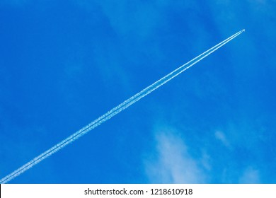 An airplane and a trail from an airplane in a blue sky